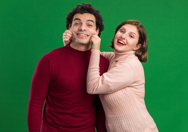 Młoda para na walentynki uśmiechnięty mężczyzna figlarna kobieta patrząca na przednią kobietę chwytającą męskie policzki odizolowane na zielonej ścianie