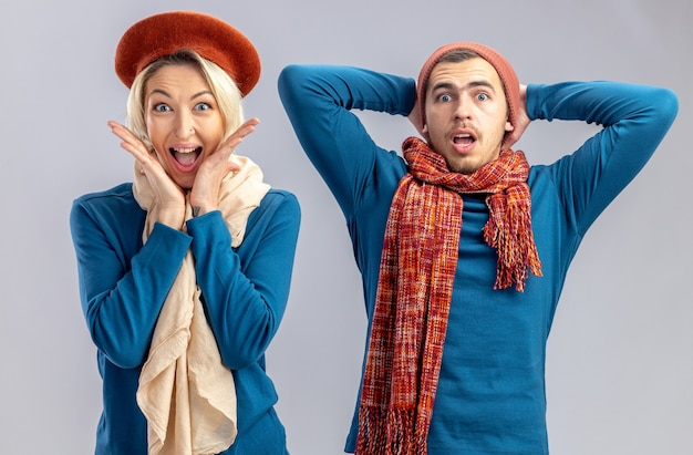 Młoda para na walentynki w kapeluszu z szalikiem zaskoczona dziewczyna kładzie ręce na policzku przestraszony facet kładzie rękę na głowie na białym tle