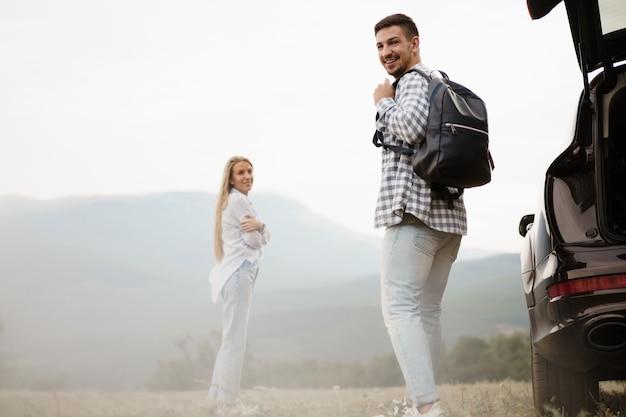 Młoda para na wycieczce, relaksując się i podziwiając widok na góry