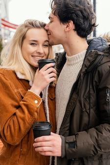 Młoda para na zewnątrz, ciesząc się filiżanką kawy