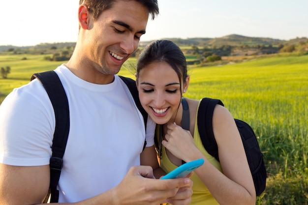 Młoda para na zewnątrz patrząc na telefon komórkowy