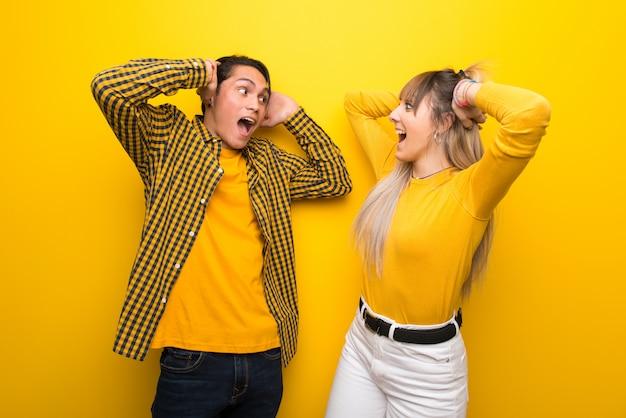 Młoda para na żywe żółte tło z niespodzianką i zszokowany