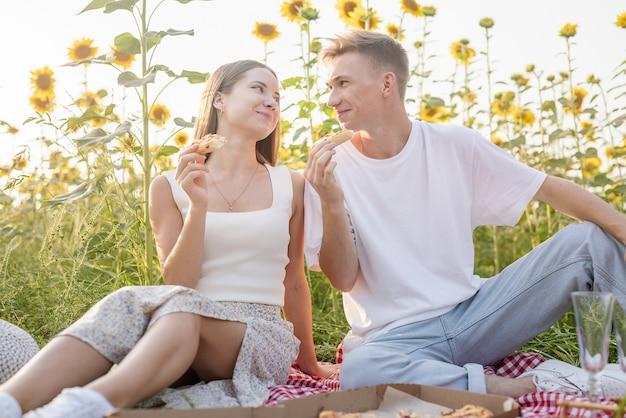 Młoda para nastolatków w białe koszule piknik na polu słonecznika w zachód słońca. jedzenie pizzy i picie szampana