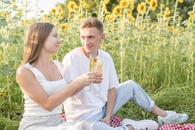 Młoda para nastoletnia piknik na polu słonecznika w zachód słońca. jedzenie pizzy i picie szampana