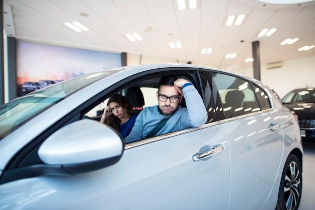 Młoda para nie może się porozumieć co do nowego samochodu, który chce kupić