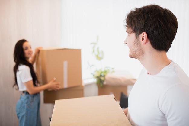 Młoda para, niosąc duży karton w nowym domu. przeprowadzki.