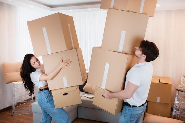 Młoda para niosąca wiele kartonów jeden po drugim w nowym domu. przeprowadzka