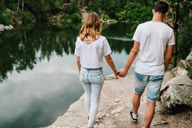 Młoda para nogi na kamieniu w pobliżu jeziora