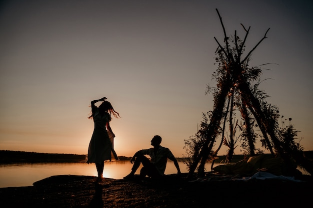Młoda para obejmuje w wodzie na zachód słońca. dwie sylwetki przed słońcem. romantyczna historia miłosna. wigwam na kamieniu.
