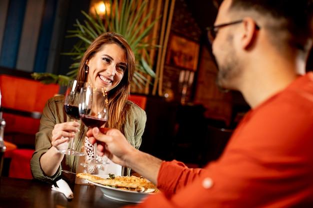 Młoda para obiad w restauracji z kieliszkami czerwonego wina
