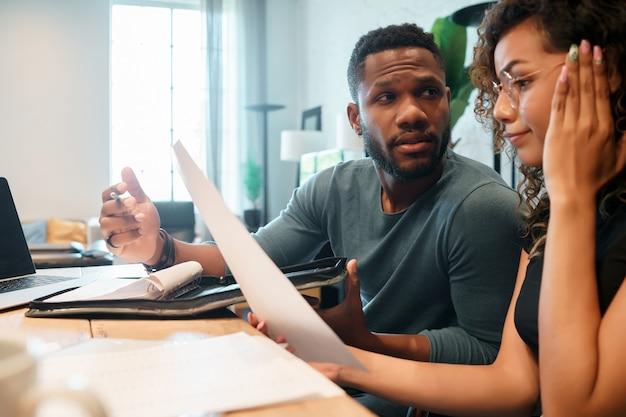 Młoda para obliczania i płacenia rachunków na laptopie z domu. para planuje budżet miesięczny.