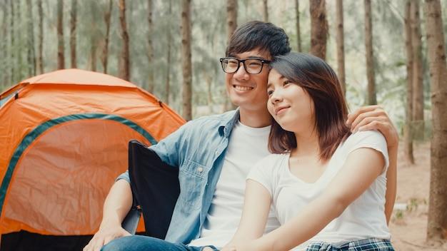 Młoda para obozowiczów z azji siedzi na krzesłach przy namiocie w lesie