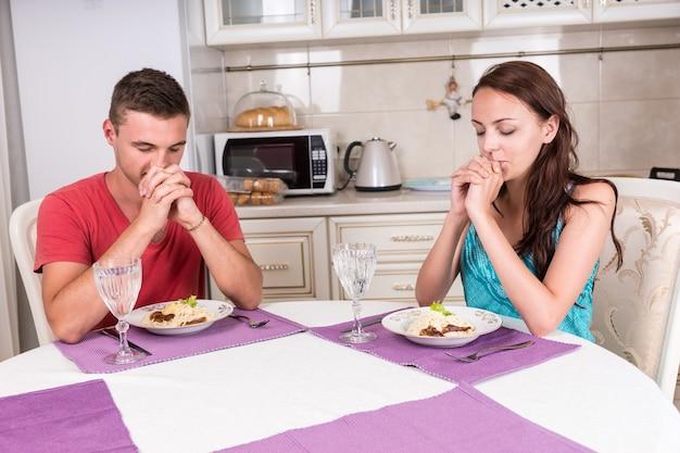 Młoda para odmawia łaskę przed rozpoczęciem posiłku siedząc z zamkniętymi oczami i dziękując