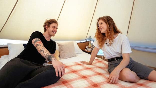 Młoda para odpoczywa na łóżku w namiocie w glampingu uśmiecha się i śmieje