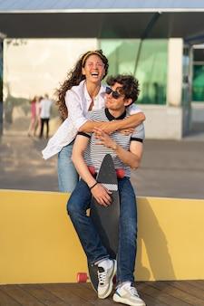 Młoda para odpoczywa po longboardzie szczęśliwi mężczyzna i kobieta w okularach przeciwsłonecznych cieszą się zachodem słońca i przytulają się