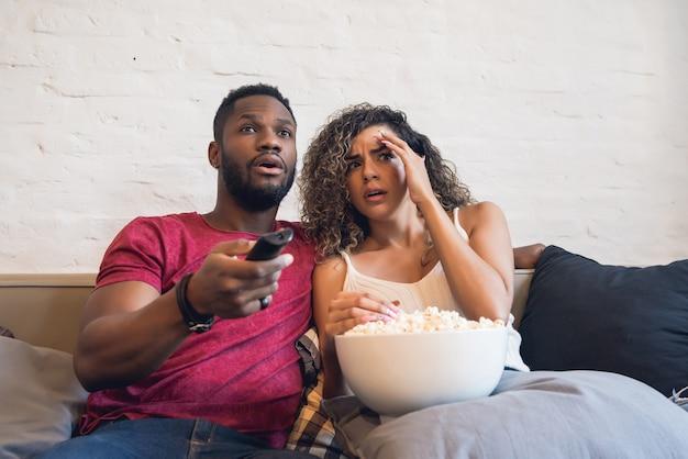 Młoda para ogląda horror siedząc na kanapie w domu.