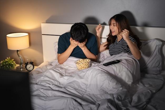 Młoda para ogląda telewizję sportową na łóżku z różnymi emocjami wygranej i przegranej