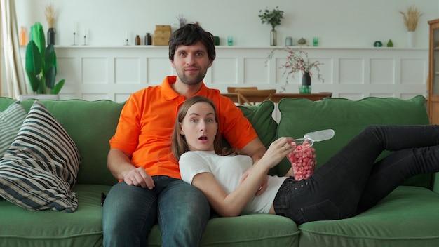 Młoda para ogląda telewizję z popcornem na kanapie