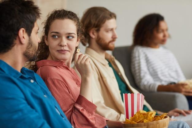 Młoda para ogląda telewizję z przyjaciółmi, siedząc na przytulnej kanapie w domu i delektując się przekąskami