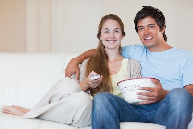 Młoda para oglądania telewizji jedząc popcorn