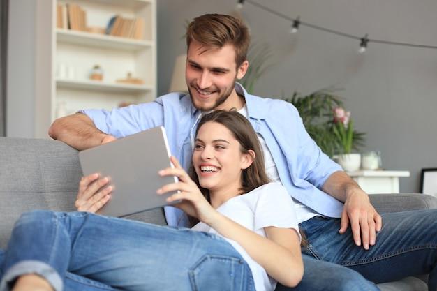 Młoda para oglądania treści multimedialnych online w tablecie, siedząc na kanapie w salonie.