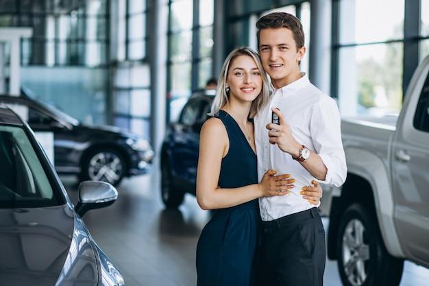 Młoda para omija samochód w salonie samochodowym