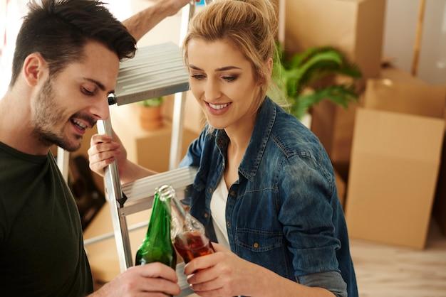 Młoda para opiekająca piwo w nowym domu