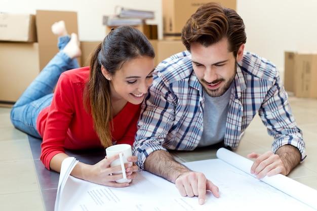 Młoda para patrząc na plany ich nowego domu