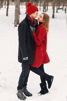 Młoda para patrząc na siebie na śnieżnym polu