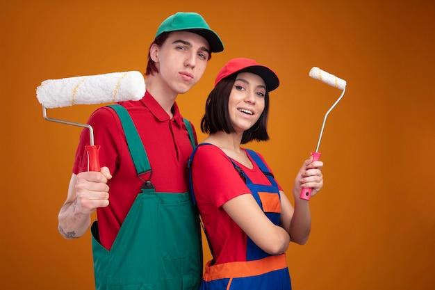 Młoda para pewny siebie facet i podekscytowana dziewczyna w mundurze pracownika budowlanego i czapce stojącej w widoku profilu, trzymając wałek do malowania, patrząc na kamerę odizolowaną na pomarańczowej ścianie