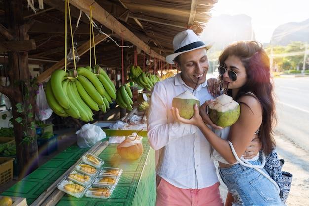 Młoda para pić kokosowy obejmowanie na tajlandia ulicznym rynku, turysta mężczyzna i kobieta w traditiona