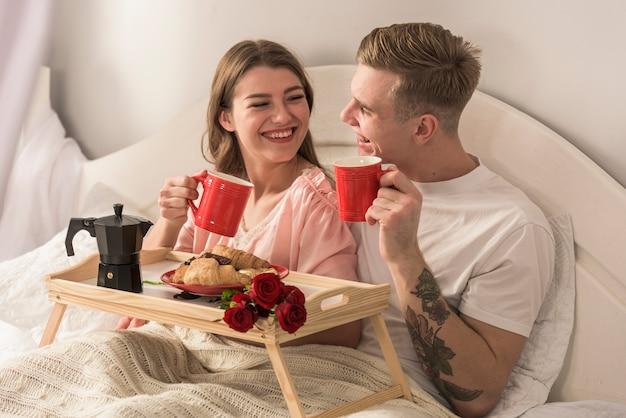 Młoda para picia kawy w łóżku