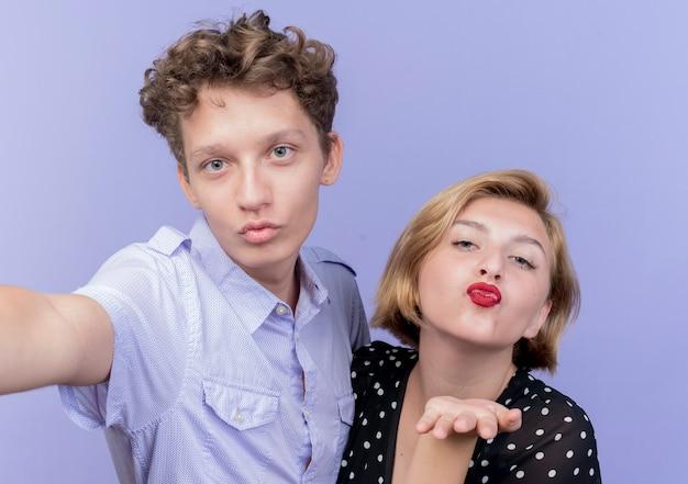 Młoda para piękny hapy w miłości całusy stojąc na niebieskiej ścianie