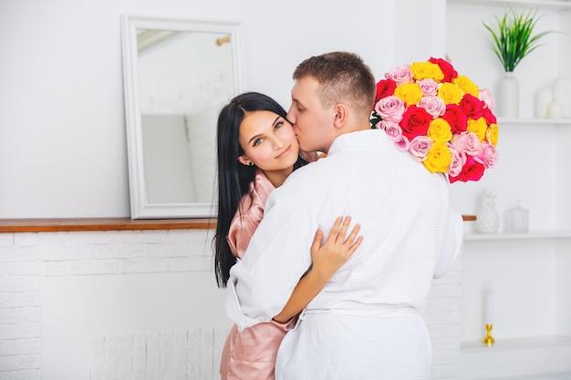 Młoda para piękny mężczyzna daje kobiecie kwiaty na wakacje w domu