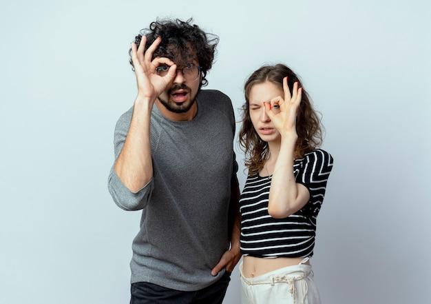 Młoda para piękny mężczyzna i kobieta, patrząc na kamery, dokonywanie ok znak stojący na białym tle