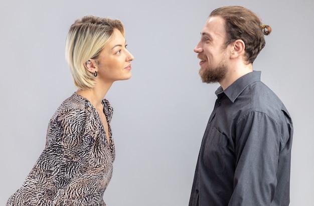 Młoda para piękny mężczyzna i kobieta, patrząc na siebie, uśmiechając się radośnie świętuje walentynki stojąc na białej ścianie