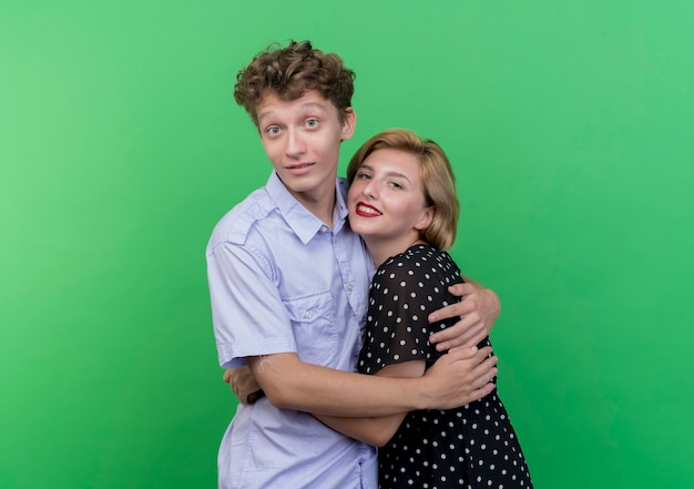 Młoda para piękny mężczyzna i kobieta stojąc razem hapy w miłości przytulanie stojąc na zielonej ścianie