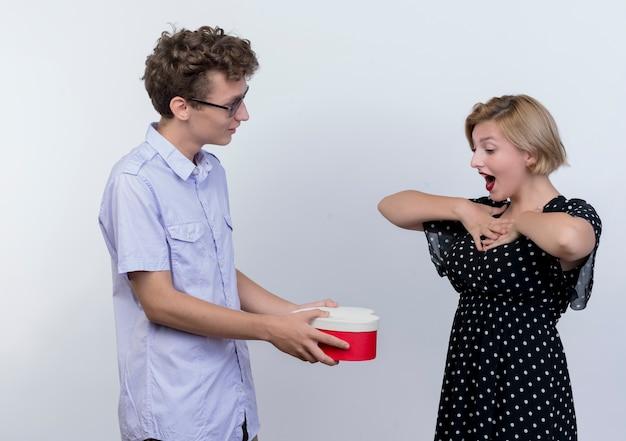 Młoda para piękny mężczyzna i kobieta stojąc razem mężczyzna dając prezent pudełko do swojej zaskoczonej dziewczyny na białej ścianie