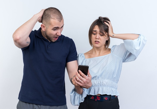 Młoda para piękny mężczyzna i kobieta ze smartfonem patrząc na to mylić z rękami na głowach stojących