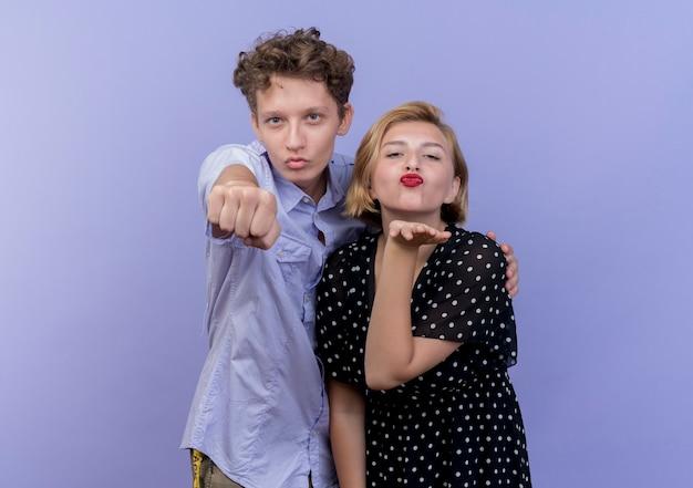 Młoda para piękny mężczyzna pokazujący pięść i kobieta dmuchanie buziaka ręką przed nią na niebieskiej ścianie