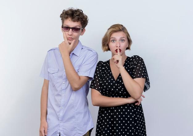 Młoda para piękny mężczyzna z zamyślonym wyrazem twarzy i kobieta robi gest ciszy z palcem na ustach stojąc na białej ścianie