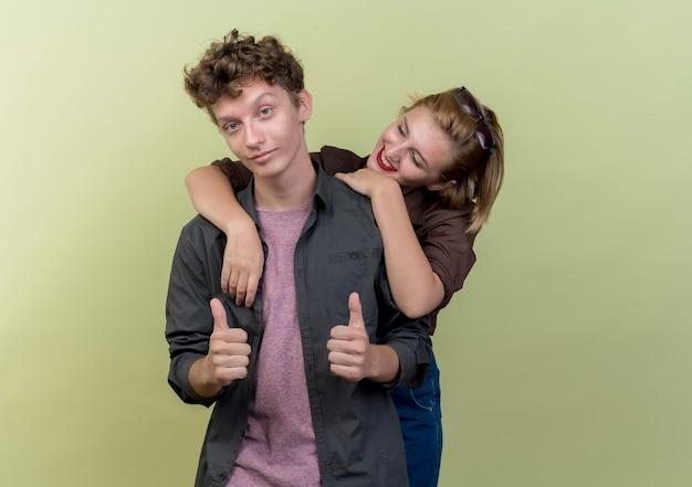 Młoda para piękny na sobie ubranie chłopak i dziewczyna szczęśliwy w miłości dziewczyna przytulanie swojego chłopaka, podczas gdy on pokazuje kciuki do góry nad światłem