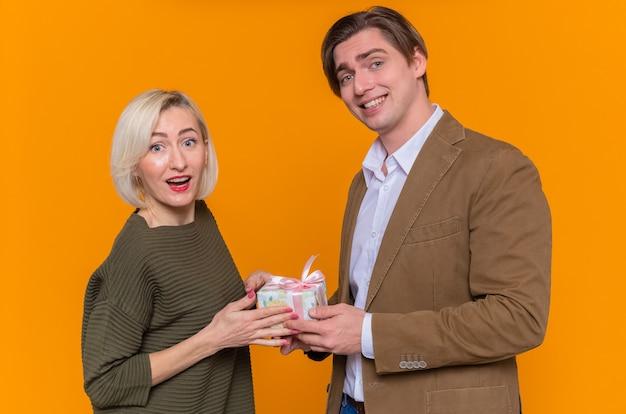 Młoda para piękny szczęśliwy człowiek dając prezent swojej uroczej uśmiechniętej dziewczynie
