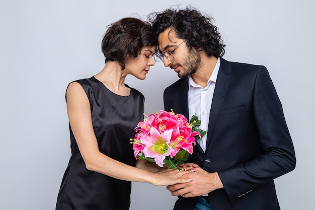 Młoda para piękny szczęśliwy mężczyzna daje bukiet kwiatów swojej uroczej dziewczynie szczęśliwy w miłości świętuje międzynarodowy dzień kobiet 8 marca stojąc na białym tle