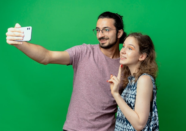 Młoda para piękny w ubranie mężczyzna i kobieta, szczęśliwy człowiek robi im zdjęcie za pomocą swojego smartfona stojącego na zielonym tle