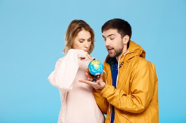 Młoda para piękny, wskazując w różnych miejscach małego globu nad niebieską ścianą mężczyzna ubrany w płaszcz przeciwdeszczowy.