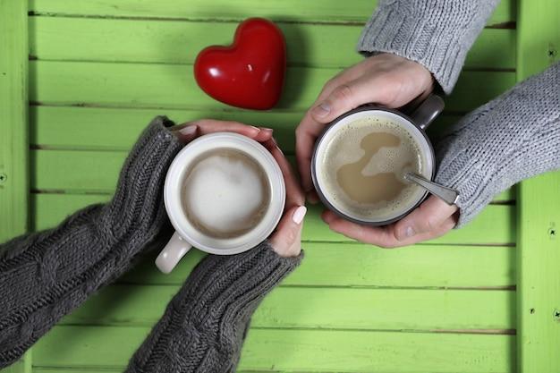 Młoda para pije gorącą kawę przy drewnianym stole na randce