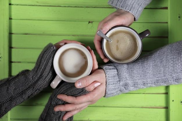 Młoda para pije gorącą kawę przy drewnianym stole na randkę