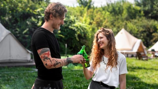 Młoda para pije piwo, uśmiechając się, brzęk butelek. wokół zieleń. glamping