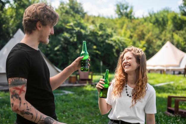 Młoda para pije piwo, uśmiechając się. wokół zieleń. glamping